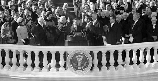In this Jan. 20, 1961, black and white file photo,John F. Kennedy takes his oath as President of the United States from Chief Justice Earl Warren in Washington. Watching in the front from from left are: Lady Bird Johnson, Jacqueline Kennedy; former President Dwight Eisenhower; Warren; James Browning, clerk of Supreme Court; Kennedy; Vice President Lyndon Johnson, outgoing Vice president and Kennedy's defeated presidential opponent Richard M Nixon, Sen John Sparkman, D- Ala., and former President Harry Truman. Photo: AP