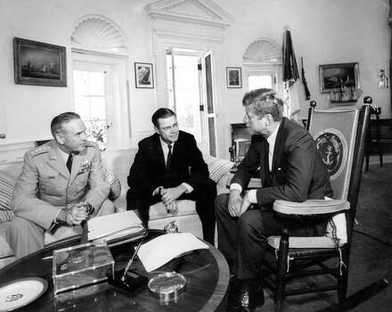 In this Oct. 2, 1963 black-and-white photo, provided by the John F. Kennedy Presidential Library and Museum, shows President John F. Kennedy, right, meeting with Joint Chiefs Chairman Gen. Maxwell D. Taylor, left, and Defense Secretary of Defense Robert S. McNamara, in the Oval Office of the White House in Washington. Photo: Abbie Rowe, AP / National Park Service via JFK Library