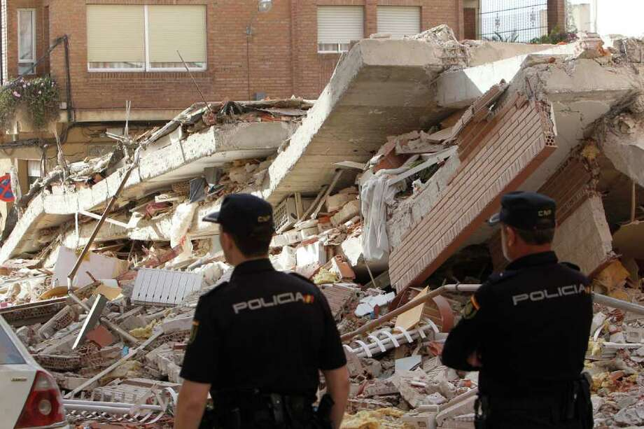 Two spanish police officers looks at the rubble of a fallen building in Lorca, Spain, on Thursday, May 12, 2011. Two earthquakes shook southeastern Spain in quick succession Wednesday, killing people, injuring dozens and causing extensive damage to buildings.  It was the largest number of earthquake-related deaths in Spain over 50 years. Photo: Alberto Saiz, AP / AP
