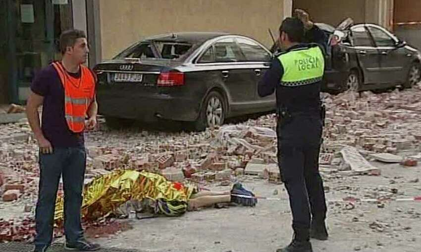 Emergency personnel attend the scene as a body lies covered on the ground after an earthquake in Lorca Spain in this image taken from TV Wednesday May 11, 2011. Two earthquakes struck southeast Spain in quick succession Wednesday, killing several people, and injuring dozens and causing major damage to buildings, officials said. The epicenter of the quakes with magnitudes of 4.4 and 5.2 was close to the town of Lorca, and the second came about two hours after the first. (AP Photo/Atlas T V, via APTN) TV OUT SPAIN OUT