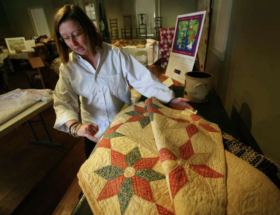 Laura Macaluso discusses a signature quilt from 1847, one of the many qults which will be on display as part of the Norwalk Quilt Trail exhibit at the Norwalk Historical Society Town House at 2 East Wall Street. The quilt originally belonged to a member of Norwalk's Hoyt family. Signature quilts were often presented by family and friends as remembrances to one who was moving to a different part of the country. Photo: Brian A. Pounds / Connecticut Post