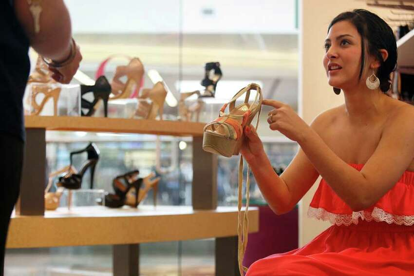 biz- Leeta Reyes, 17, asks to try on a shoe at O Shoes in the North Star Mall as she shops with fellow students on their senior trip from La Villa on Wednesday, May 11, 2011. LISA KRANTZ/lkrantz@express-news.net