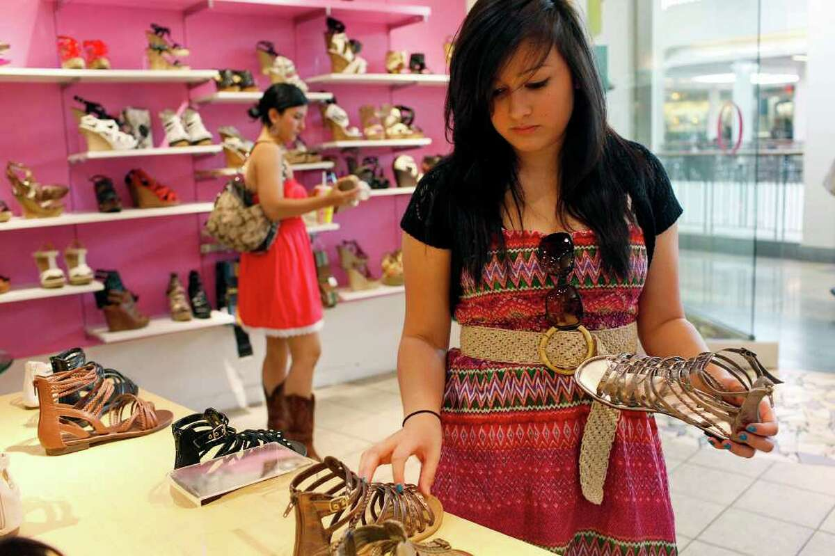 biz- Gina Solis, 18, right, and Leeta Reyes, 17, shop at O Shoes in the North Star Mall as they shop with fellow students on their senior trip from La Villa on Wednesday, May 11, 2011. LISA KRANTZ/lkrantz@express-news.net