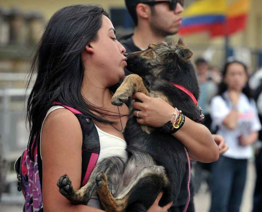 A girl kisses her pet during a protest march against animal abuse on May 10, 2011, in Bogota, Colombia. AFP PHOTO/Guillermo Legaria Photo: GUILLERMO LEGARIA, AFP/Getty Images / 2011 AFP