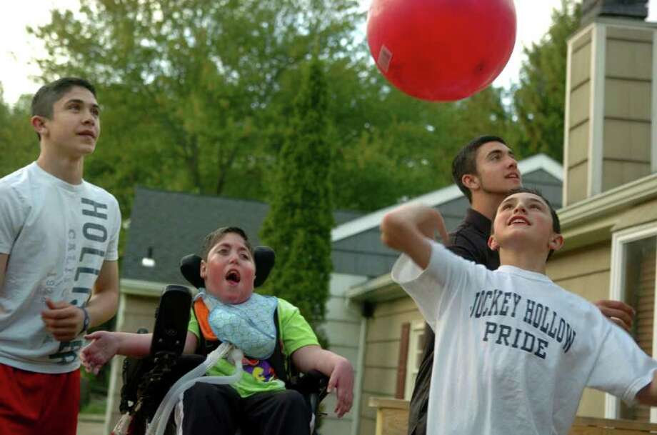 Anthony Katz enjoys the fun with his brothers (from left) Doug Jr., Frankie, and Michael, foreground, as they throw and bounce balls off of the roof at their home in Monroe, Conn. on Wednesday May 11, 2011. Anthony is 10 years old now and when he was born, he was only expected to live for a few hours. He has a rare form of muscular dystrophy called myotubular myopathy. Photo: Christian Abraham / Connecticut Post