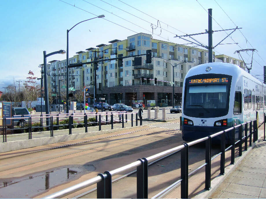 A light-rail train pulls up at the Othello Station, kitty-corner to The Station at Othello Park building. Photo: Othello Partners
