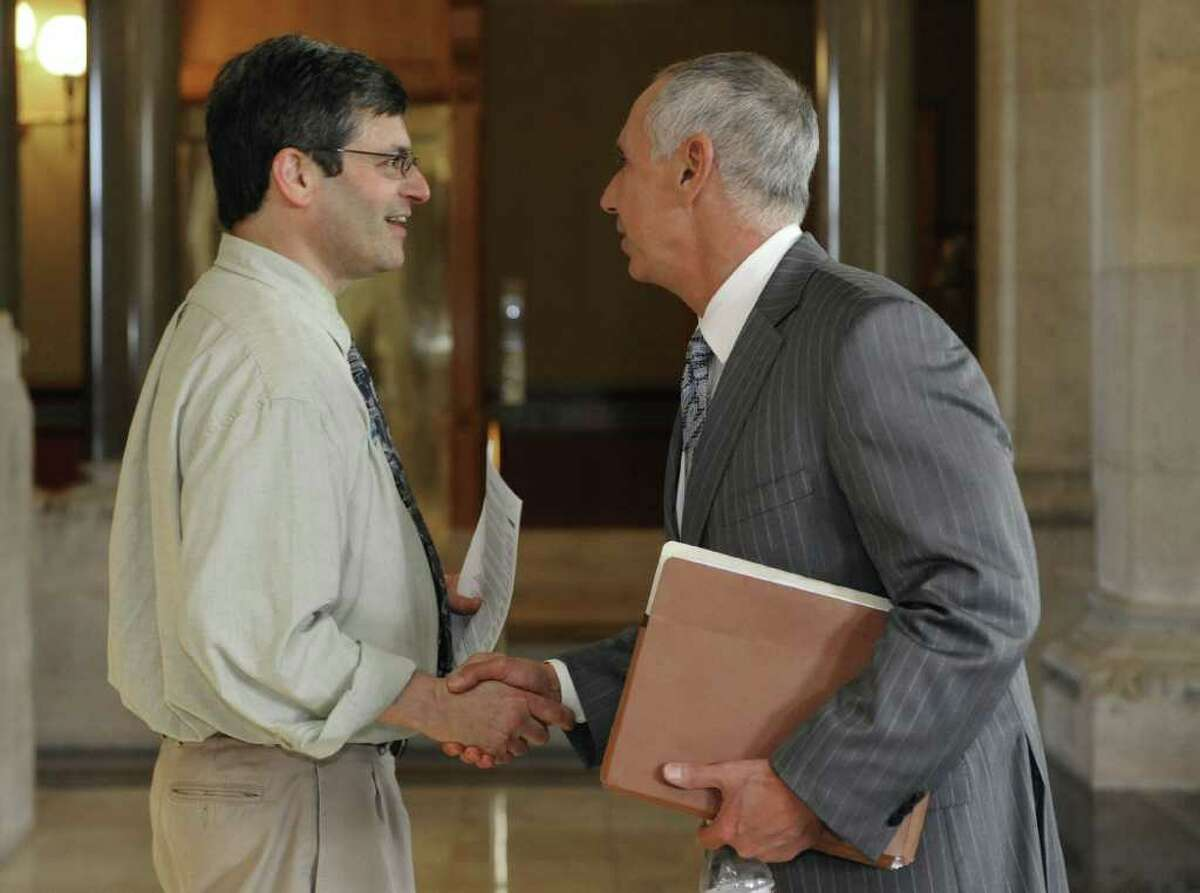 Larry Dorman, the chief spokesman for The State Employees Bargaining Agent Coalition (SEBAC), left, shakes hands with Mark Ojakian, deputy secretary of the Office of Policy and Management and chief negotiator from the governor's office for union talks at the Capitol in Hartford, Conn., Friday, May 13, 2011 Lawmakers and state employee union officials have reached an agreement that avoids mass layoffs and closes much of a looming $2 billion budget shortfall facing the state over the next two years.(AP Photo/Jessica Hill)