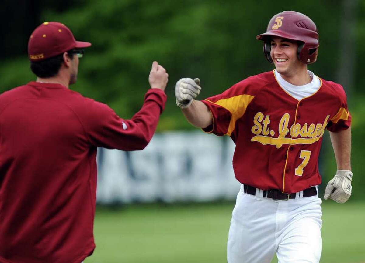 St. Joseph's Chris McCormack gets a fist bump as he rounds third base after hitting a home run during Friday's game against St. Joseph High School at Staples High School on May 13, 2011.