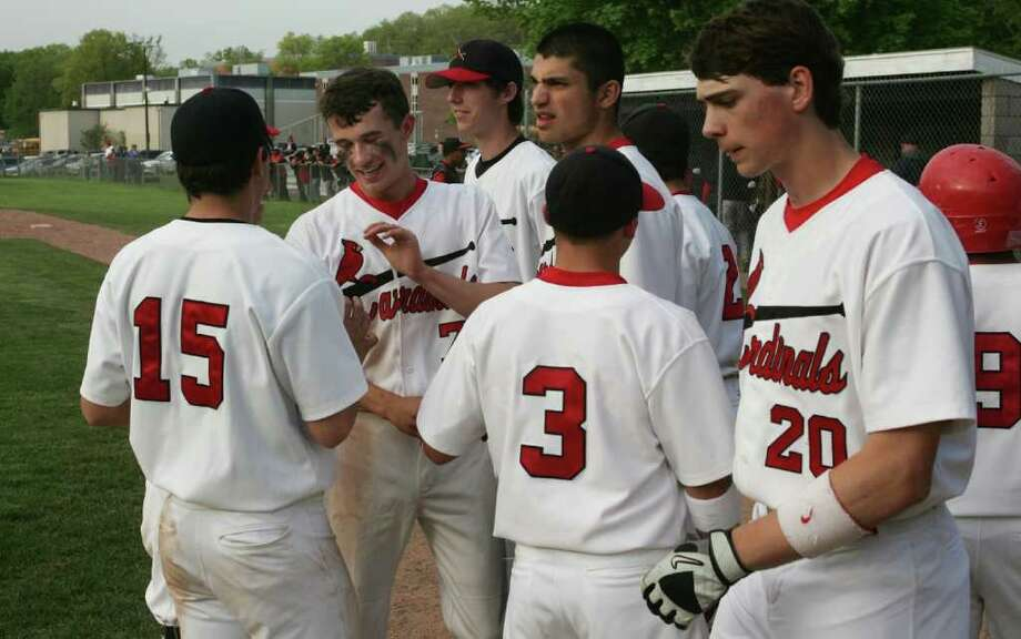Greenwich High School pitcher Dylan Callahan is congratulated after scoring the winning run in Friday afternoons extra inning game against Central. Photo: David Ames, David Ames/For Greenwich Time / Greenwich Time Freelance