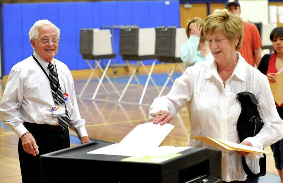 M. Jodi Rell, former governor of Connecticut, casts her vote on the budget referendum at Brookfield High School, Saturday, May 14, 2011. John Furlong, an election offical, watches at left. Photo: Michael Duffy / The News-Times