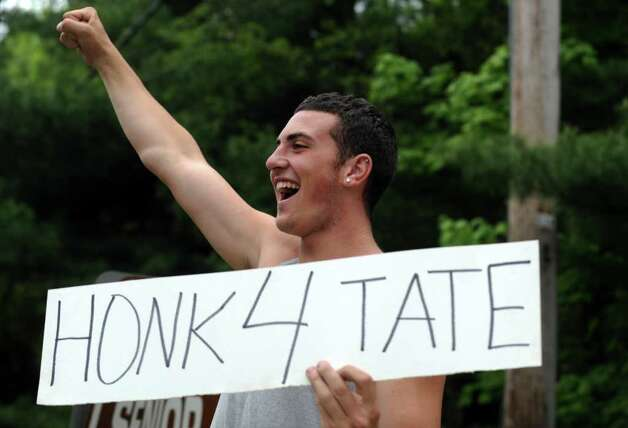 "Shelton High School senior Joe Joyce encourages passersby to ""honk 4 Tate"" outside the track team's car wash Saturday, May 14, 2011. Photo: Autumn Driscoll / Connecticut Post"