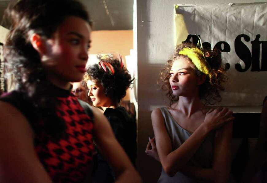 Model Malama Pono, right, waits backstage during Seattle Fashion Week's grand finale show at the Kin