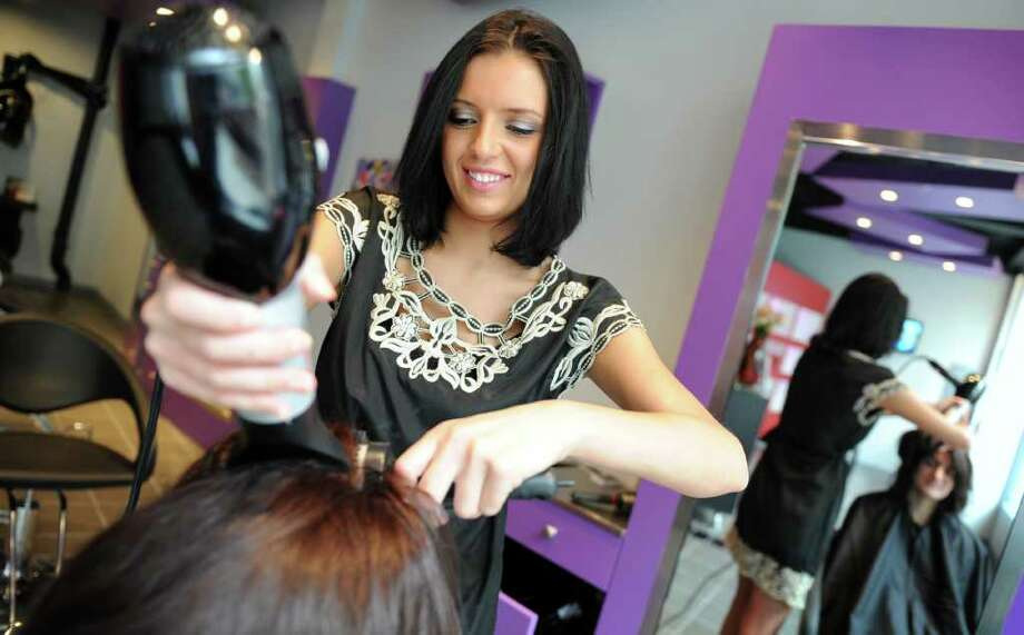 Salon owner Cynthia Gaspar styles client Jennifer Harrington's hair Saturday, May 14, 2011 at newly-opened Moda Studio in Bridgeport, Conn. Photo: Autumn Driscoll / Connecticut Post
