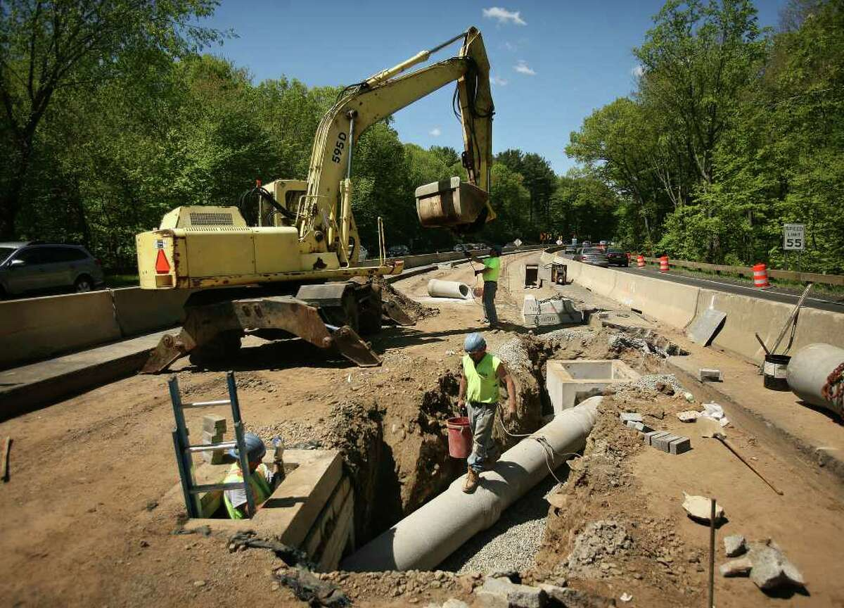 Workers install a catch basin for water run off as part of the $67 million Merritt Parkway improvement project on Thursday, May 12, 2011.