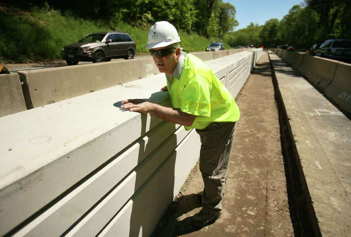 Resident engineer John O'Dierna looks down a long line of concrete barriers on the Merritt Parkway improvement project. O'Dierna said that because the barriers are installed at night when there is little light, adjustments to their placement often need to be made afterwards.