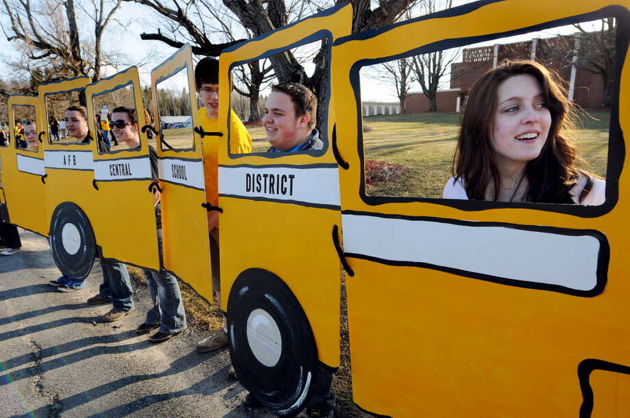 "Brittany Brisson, 17, right, joins other students as they hold up the bus from the upcoming play ""You're a Good Man Charlie Brown"" as they protest proposed school cuts on Thursday, April 7, 2011, at Galway Central School in Galway, N.Y. (Cindy Schultz / Times Union)"