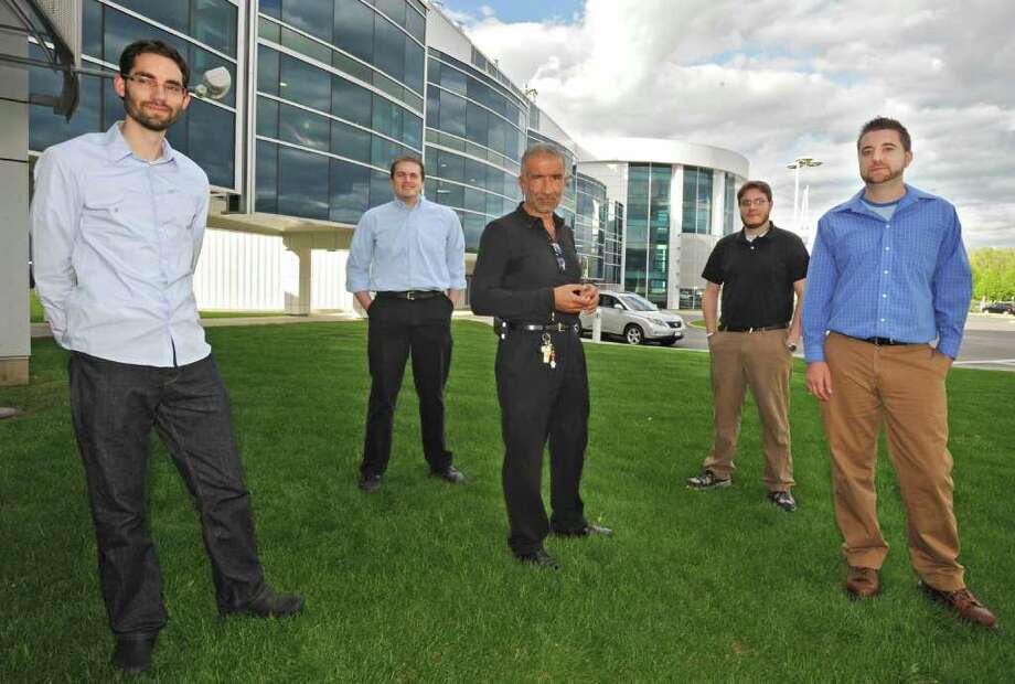 Alain Kaloyeros, chief executive officer of the University at Albany's College of Nanoscale Science and Engineering, stands in the middle of four NanoCollege grads at Albany NanoTech in Albany, N.Y. Wednesday May 11, 2011. From left, the graduates are Seth Kruger, Ben Backes, Joshua LaRose and Craig Higgins.  All have semiconductor jobs lined up in the Hudson Valley. Higgins begins working for GlobalFoundries on Monday and will eventually be located at Fab 8 in Malta. (Lori Van Buren / Times Union) Photo: Lori Van Buren