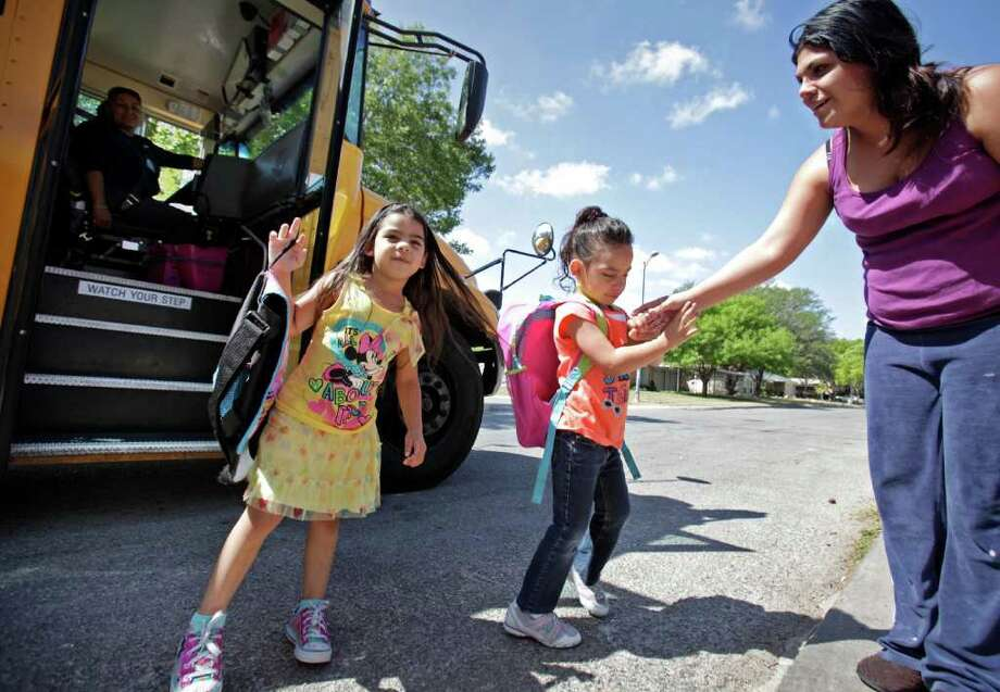 Ashley Cortez says goodbye to her twin daughters Bianca and Brianna as they get on the bus to take them to Driggers Elementary.  The district approved $2 million in cuts to the district's transportation department, Thursday, May 5, 2011. photo Bob Owen/rowen@express-news.net Photo: BOB OWEN, Bob Owen/Express-News / rowen@express-news.net