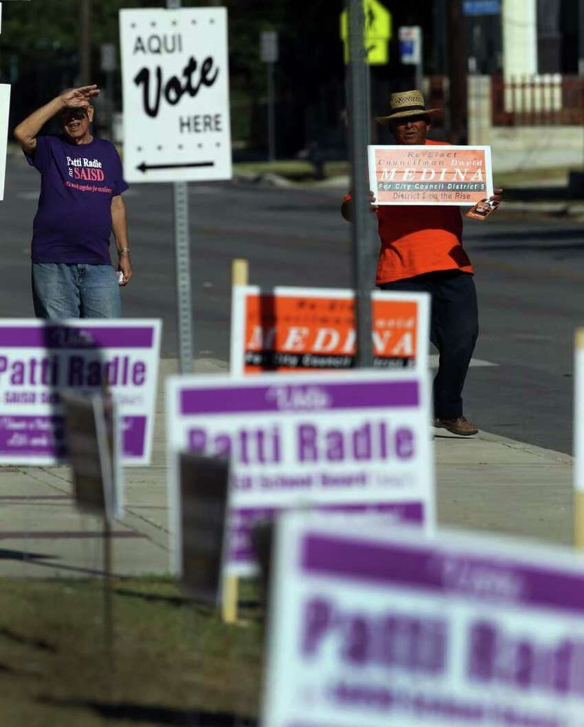 Robert Galvan (left) and George Martinez (right) stand in front of Lanier High School on Saturday, May 14, 2011 - Election Day.