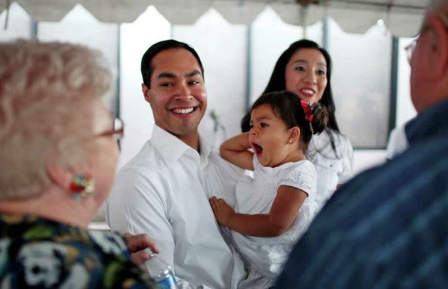 Mayor Julián Castro his 2-year-old daughter Carina and wife Erica (background) greet supporters at his campaign headquarters on Saturday, May 14, 2011. Photo: Edward A. Ornelas/Express-News / SAN ANTONIO EXPRESS-NEWS (NFS)