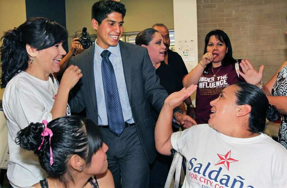 Rey Saldaña gets high-fives from extended family members as he thanks supporters at the Southside YMCA on Southcross on Saturday, May 14, 2011. Photo: Tom Reel/Express-News / © 2011 San Antonio Express-News