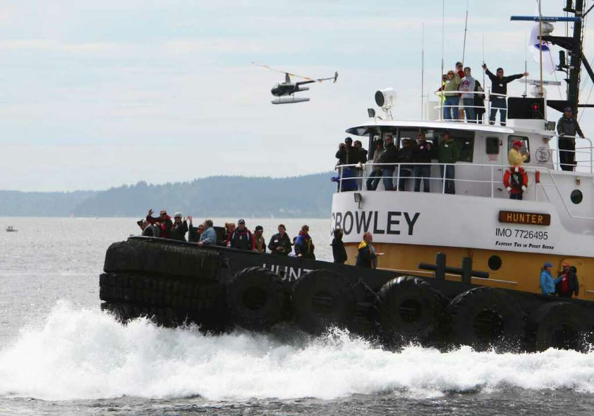 The Crowley tug Hunter powers across the finish line during the Seattle Maritime Festival tug boat races on Saturday, May 14, 2011 on the Seattle waterfront. The annual event featured the Quick and Dirty Boat Building Competition and the popular tugboat races. The event is organized by the Seattle Propeller club and the Port of Seattle and showcases Seattle's maritime industry.