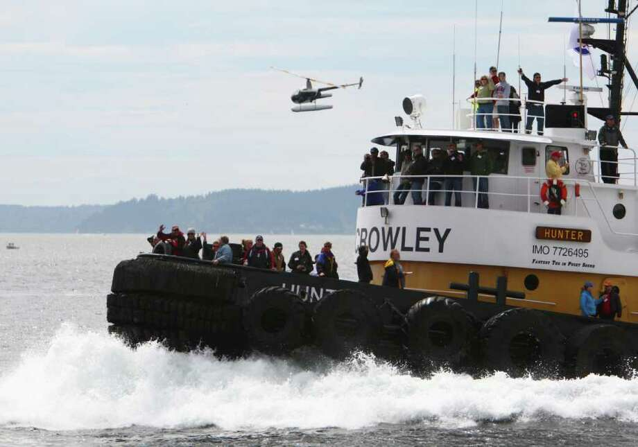 The Crowley tug Hunter powers across the finish line during the Seattle Maritime Festival tug boat races on Saturday, May 14, 2011 on the Seattle waterfront. The annual event featured the Quick and Dirty Boat Building Competition and the popular tugboat races. The event is organized by the Seattle Propeller club and the Port of Seattle and showcases Seattle's maritime industry. Photo: JOSHUA TRUJILLO / SEATTLEPI.COM