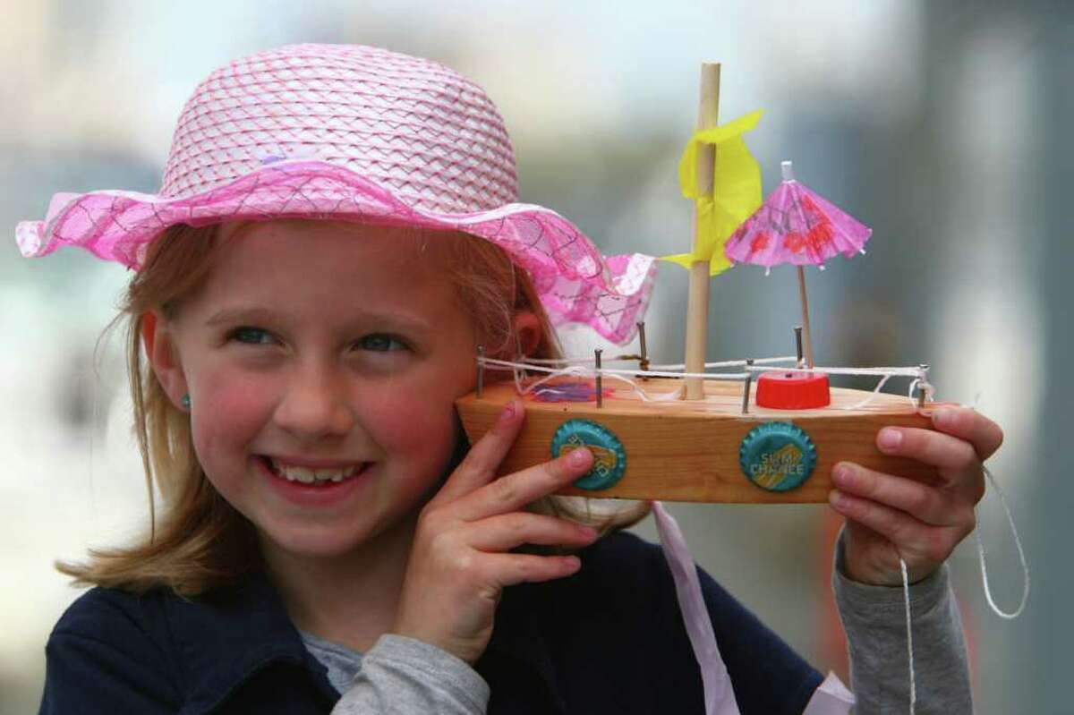Adrianne Carpenter, 7, of Seattle holds a boat she made during the Seattle Maritime Festival on Saturday, May 14, 2011 on the Seattle waterfront. The annual event featured the Quick and Dirty Boat Building Competition and the popular tugboat races. The event is organized by the Seattle Propeller club and the Port of Seattle and showcases Seattle's maritime industry.