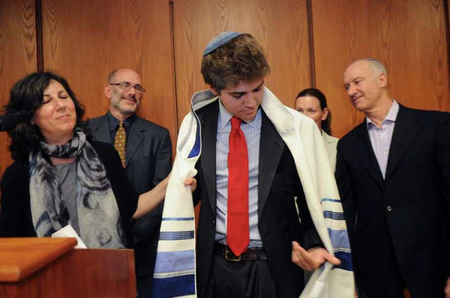 Aner Shofty, 18, of Israel, receives his tallis at his Bar Mitzvah at Greenwich Town Hall after at the celebration to honor Israel and its 63rd year of independence on Sunday, May 15, 2011. Shofty received his tallis from his host famlies, from left, Debra Fram, Eric Schwartz, Bryanna and Jonathan Kallman. Photo: Helen Neafsey / Greenwich Time