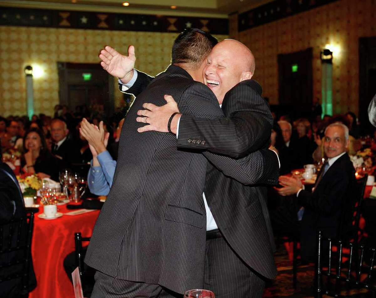 Harlandale ISD Superintendent Robert Jaklich, right, hugs Board President Anthony Alcoser after the district won the Large District category of the 10th annual H-E-B Excellence in Education Awards in Austin on  Sunday. JERRY LARA/glara@express-news.net