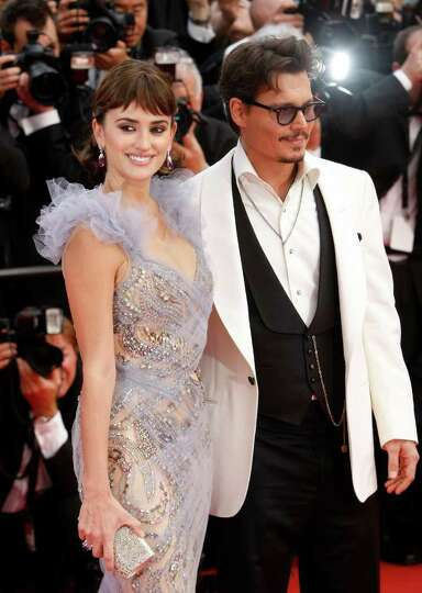 Actors Penelope Cruz, left, and Johnny Depp pose on the red carpet for the screening of Pirates of t