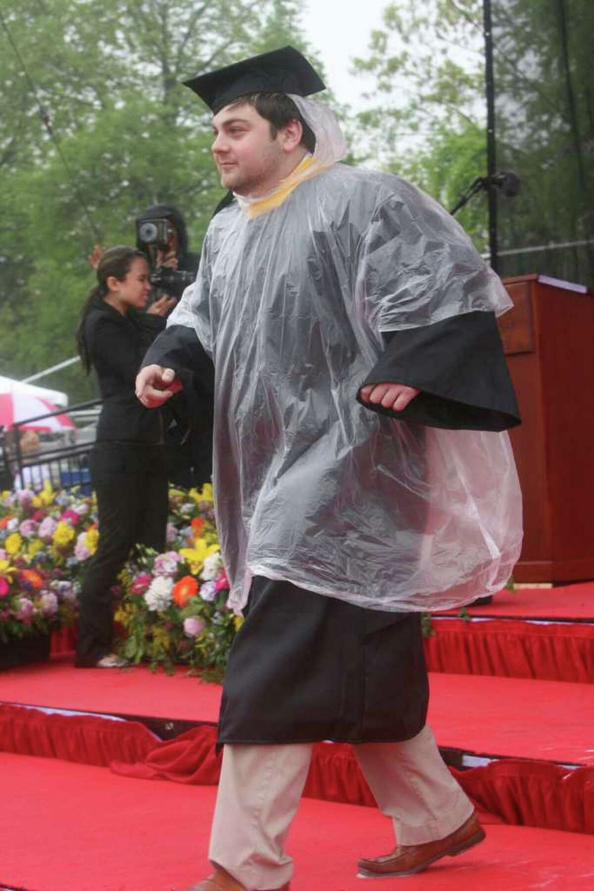 Jacob Aaron, of Weston, tries to stay dry during the SHU Commencement ceremony on Sunday, May 15, 2011.