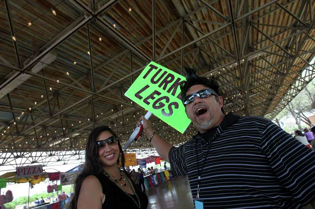 Raymond Reyna (right) advertises turkey legs and chicken on a stick (other side of sign) at Rosedale Park Sunday May 15, 2011 during the last day of the Tejano Conjunto Festival. Keeping Reyna company is Leianni de Leon (left). The festival began last Thursday. JOHN DAVENPORT/jdavenport@express-news.net