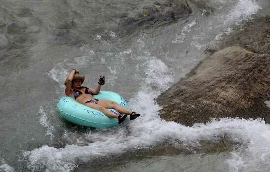 A woman slips past the tube chute on the Comal River in Prince Solms Park on Labor Day in New Braunfels, Texas on Monday, Sept. 6, 2010.  Kin Man Hui/kmhui@express-news.net Photo: KIN MAN HUI, SAN ANTONIO EXPRESS-NEWS / San Antonio Express-News