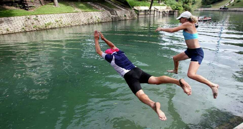 A pair of swimmers leap into the Comal River. (File photo)