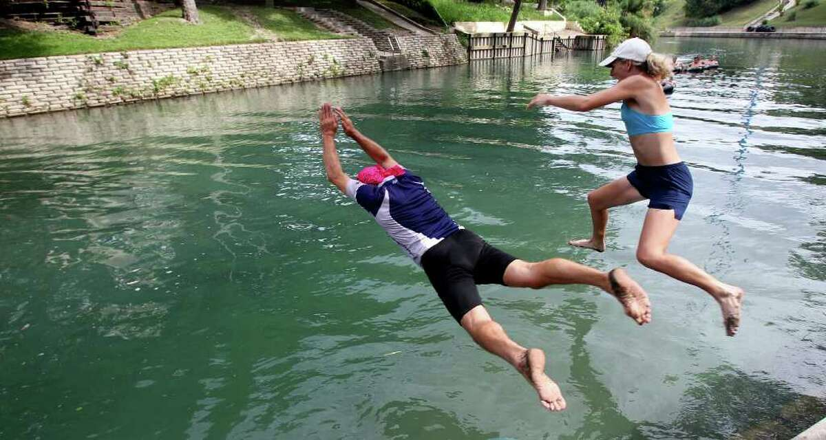 A pair of swimmers leap for the water as New Braunfels leaders mark the opening of the Comal River for tubing with a jump in at the Rapids at Schlitterbahn's on June 24, 2010. Tom Reel/Staff
