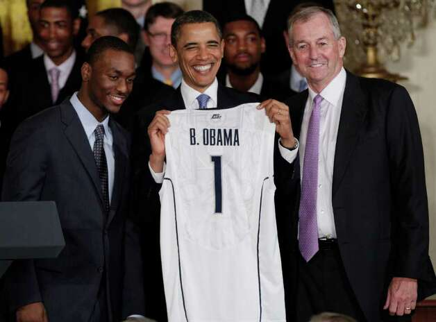 President Barack Obama, center, smiles with a jersey given to him by guard Kemba Walker, left, and coach Jim Calhoun as Obama greeted the Connecticut men's basketball team in the East Room of the White House, Monday, May 16, 2011, in Washington.  (AP Photo/Carolyn Kaster) Photo: Carolyn Kaster, AP / AP