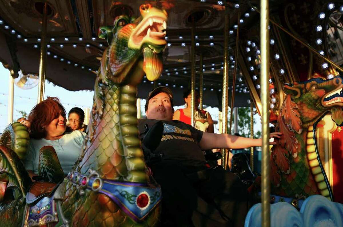 Cynthia Bonilla (left) and her son Fernando Bonilla enjoy the carousel during the grand opening of Morgan's Wonderland in 2010. (File photo)