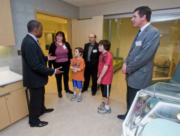 Dr. Edward James, chief of the neo-natal intensive care unit at Danbury Hospital, welcomes Nancy Matzinger, son Jacob, 8, husband Richard and son Ryan, 12, of Danbury, as Dr. John Murphy, president of the Western Connecticut Health Network, watches during the grand opening of the new neo-natal intensive care unit. The Matzinger family used the old NICU at the hospital.  Monday, May 16, 2011 Photo: Scott Mullin / The News-Times Freelance