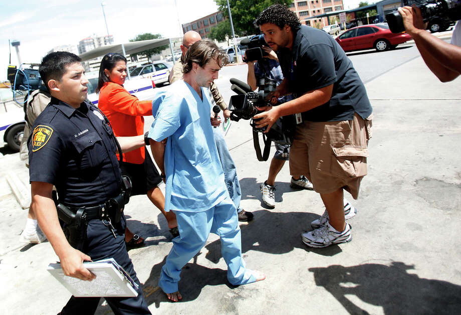 Christopher Allgood keeps his head lowered as he passes by the media while being escorted from SADP headquarters by an offcier on July 5, 2009, the day of the three slayings. Photo: Express-News File Photo