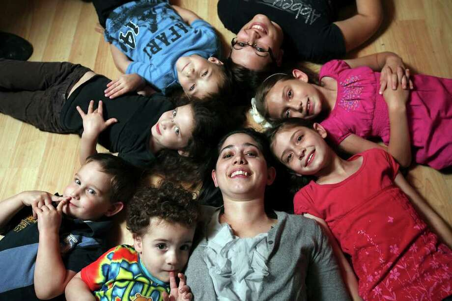 Melissa Anderson (bottom center) poses with her children,  John, 2 (clockwise from bottom); Timothy, 3;  Arabella, 5; Samuel, 6;  Kayli, 20, a sister she adopted; Elizabeth, 9; and Magdalyne, 8.  (PHOTO BY EDWARD A. ORNELAS/eaornelas@express-news.net) Photo: EDWARD A. ORNELAS, Edward A. Ornelas/Express-News / SAN ANTONIO EXPRESS-NEWS (NFS)