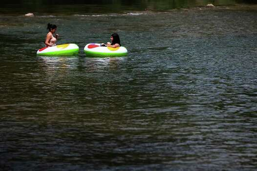 Two individuals relax while floating along the Guadalupe River at Camp Huaco Springs near New Braunfels, Texas on Monday, Sept. 6, 2010.  Kin Man Hui/kmhui@express-news.net Photo: KIN MAN HUI, SAN ANTONIO EXPRESS-NEWS / San Antonio Express-News