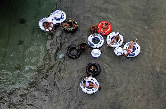 A group floats along the Comal River in Prince Solms Park on Labor Day in New Braunfels, Texas on Monday, Sept. 6, 2010.  Kin Man Hui/kmhui@express-news.net Photo: KIN MAN HUI, SAN ANTONIO EXPRESS-NEWS / San Antonio Express-News
