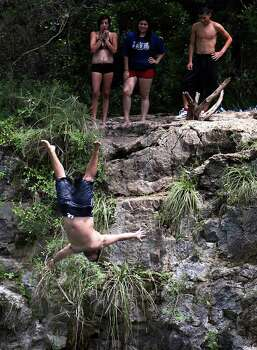 A group watches San Antonian Jonathan Llanes as he back-flips off a ledge along the Guadalupe River at Camp Huaco Springs on Labor Day near New Braunfels, Texas on Monday, Sept. 6, 2010.  Kin Man Hui/kmhui@express-news.net Photo: KIN MAN HUI, SAN ANTONIO EXPRESS-NEWS / San Antonio Express-News