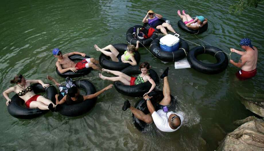 Tyrone Myers, lower center, nearly flips over backwards as he gets in his tube during a birthday tubing party for Amber Luepke, far left, at Guadalupe Canoe Livery, on the Guadalupe River, Monday, July 5, 2010. Bob Owen/rowen@express-news.net Photo: Bob Owen, SAN ANTONIO EXPRESS-NEWS / rowen@express-news.net