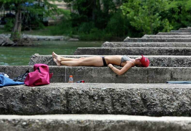 Concrete walls supporting a bridge provide a good spot for a sunbather on the Guadalupe River  on Fr