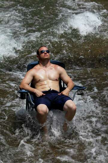 Rushing water provides a cool spot for sunbathing on the Guadalupe River  on Friday, May 28, 2010.