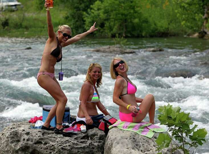 Three women rest on the rocks over rapids on the Guadalupe River on Friday, May 28, 2010.  Tom Ree