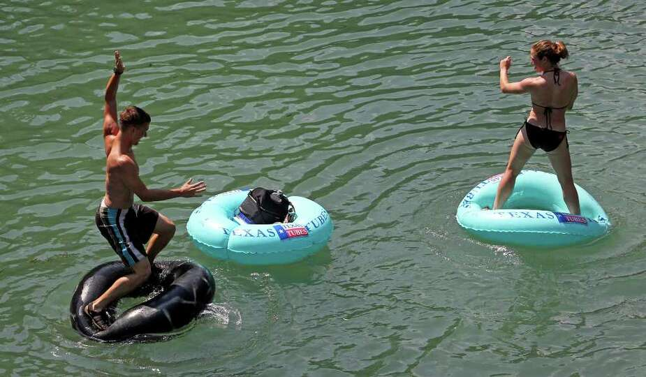 A pair of tubers on the Comal River challenge each other in standing on tubes as tubing on the Gua
