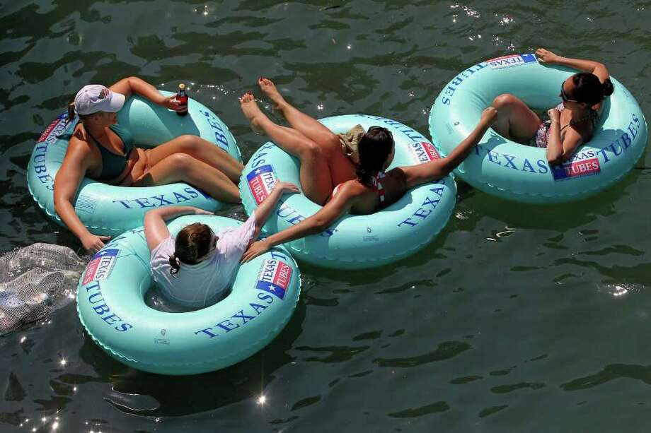 A group of tubers enjoy a calm spot on the Comal River as tubing on the Guadalupe and Comal for the holiday weekend gets started  on Friday, May 28, 2010.  Tom Reel/Staff Photo: TOM REEL, SAN ANTONIO EXPRESS-NEWS / © 2010 San Antonio Express-News